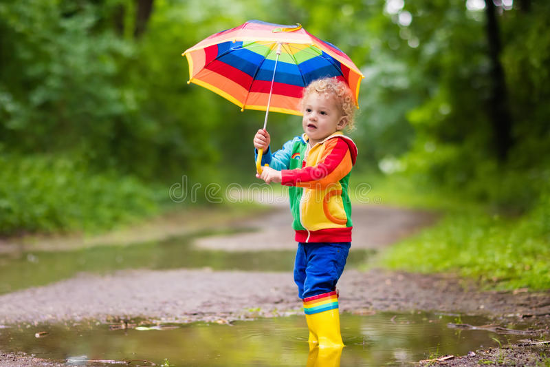 Barn som spelar i regnet under paraplyet royaltyfri foto
