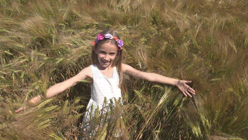 Barn som spelar i vetefältet, lycklig framsida för ung unge som ler den utomhus- ståendeflickan arkivbilder