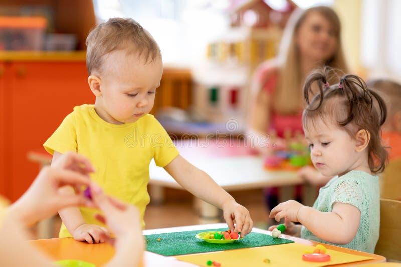 Barn som spelar lera i daghem eller på daghem royaltyfri fotografi