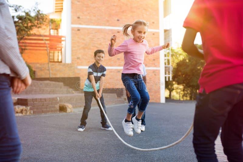 Barn som spelar med överhopprepet royaltyfri foto