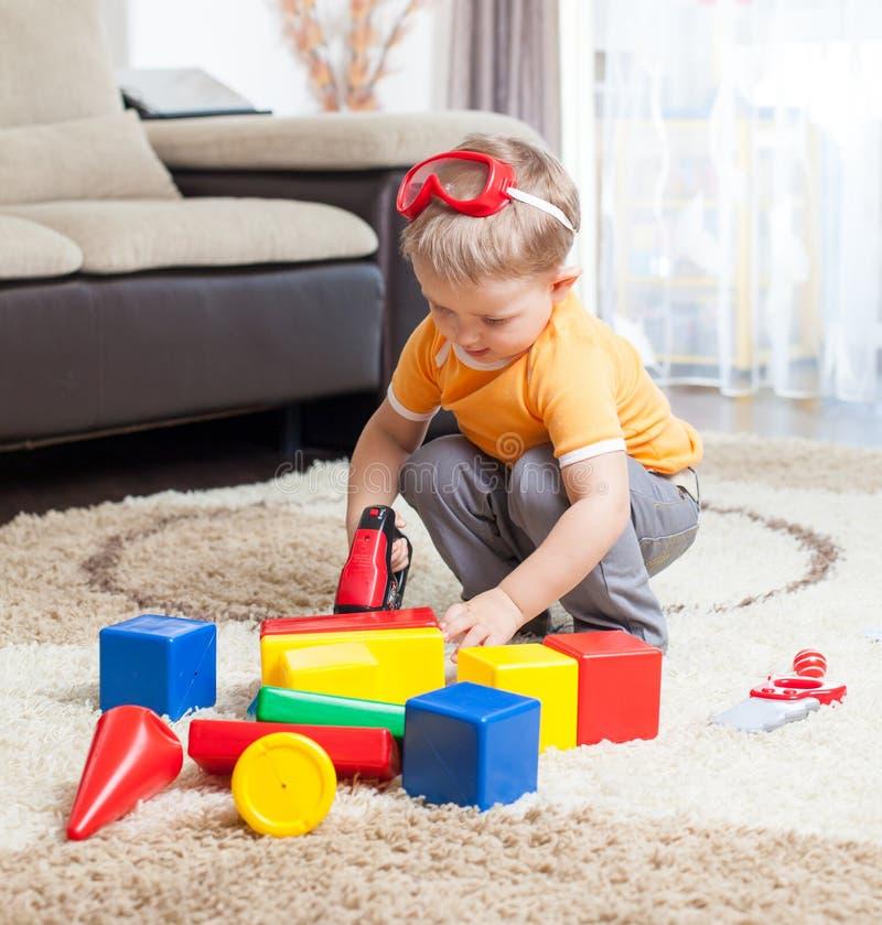 Barn som spelar med byggnadskvarter hemma. royaltyfri foto