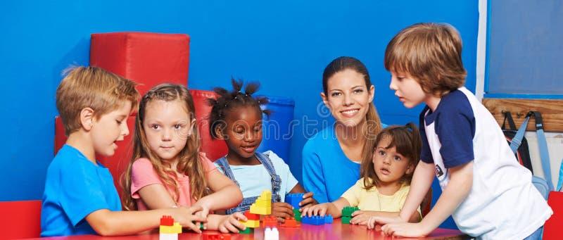 Barn som spelar med byggnadstegelstenar i barnavård arkivfoton