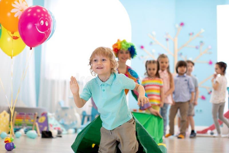 Barn som spelar med clownen p? f?delsedagpartiet i underh?llningmitt arkivbild