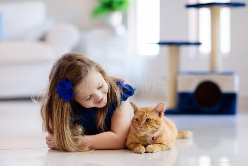 Barn som spelar med den hemmastadda katten Ungar och husdjur royaltyfri foto
