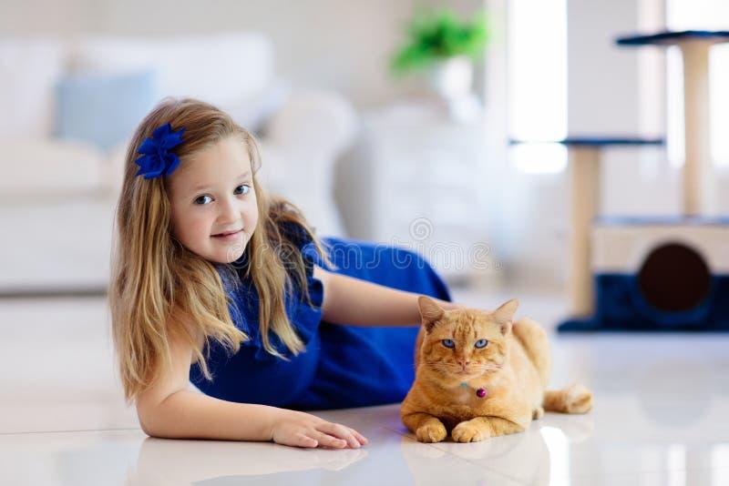Barn som spelar med den hemmastadda katten Ungar och husdjur royaltyfria bilder