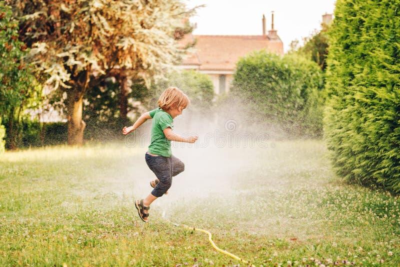 Barn som spelar med den trädgårds- spridaren royaltyfri bild
