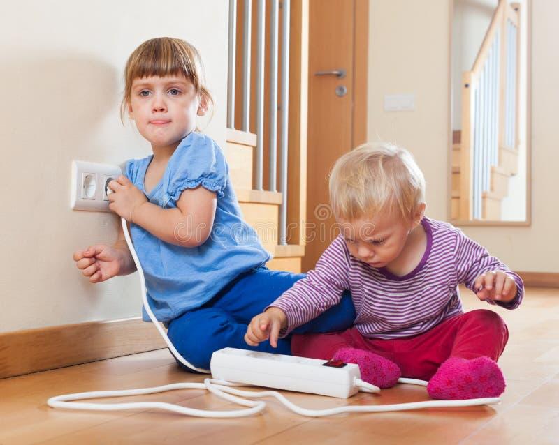 Barn som spelar med elektriskt förlängning och uttag arkivfoto