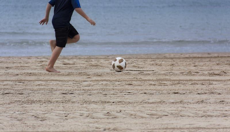Barn som spelar med en boll på stranden royaltyfria bilder
