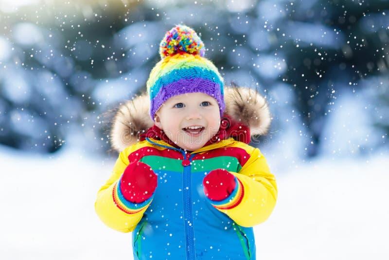 Barn som spelar med insnöad vinter ungar utomhus royaltyfri bild