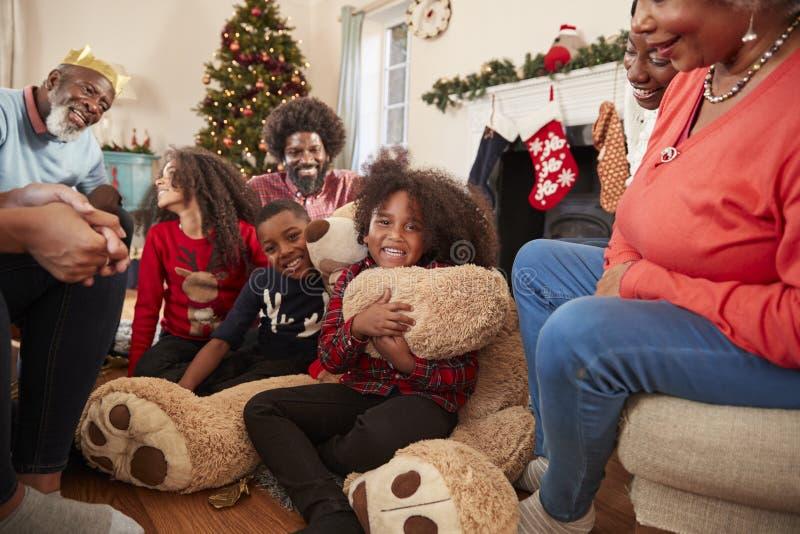 Barn som spelar med jätteTeddy Bear As Multi-Generation Family öppna gåvor på juldagen arkivfoton