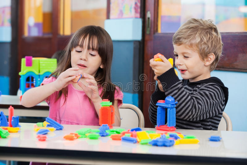 Barn som spelar med kvarter i klassrum arkivfoton