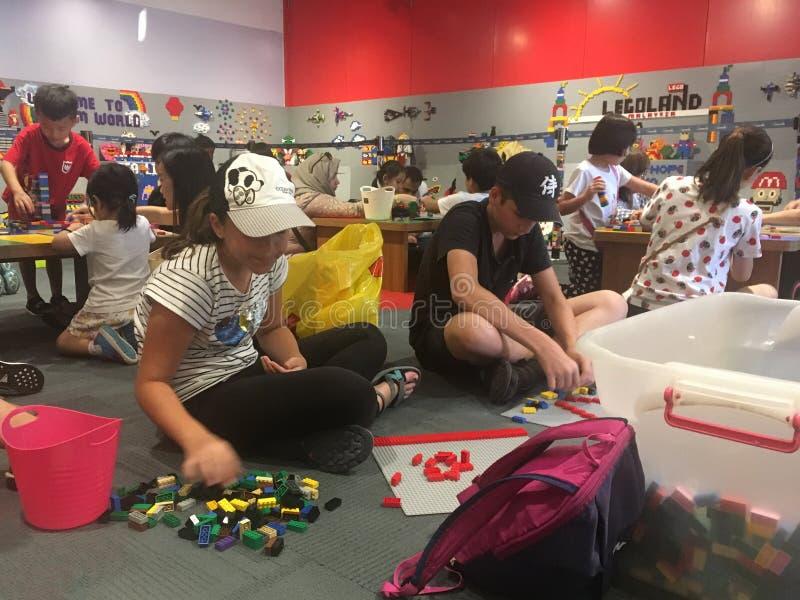 Barn som spelar med Lego delar på Legoland Malaysia fotografering för bildbyråer