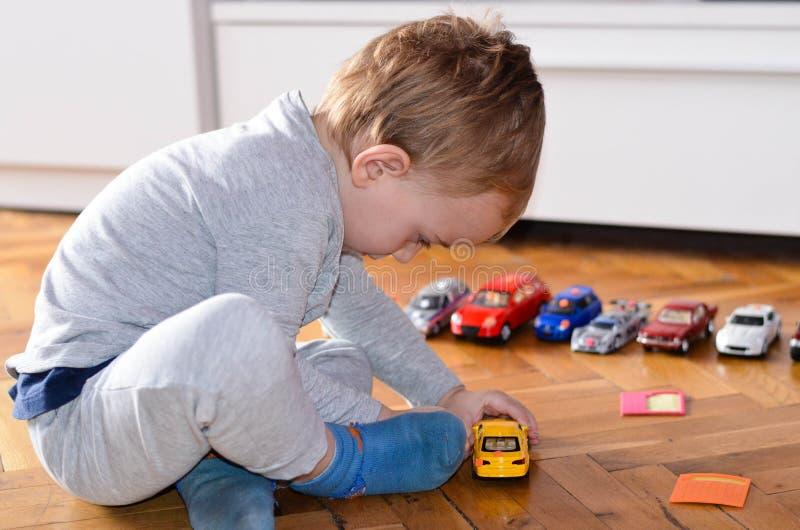 Barn som spelar med leksakbilar royaltyfri fotografi