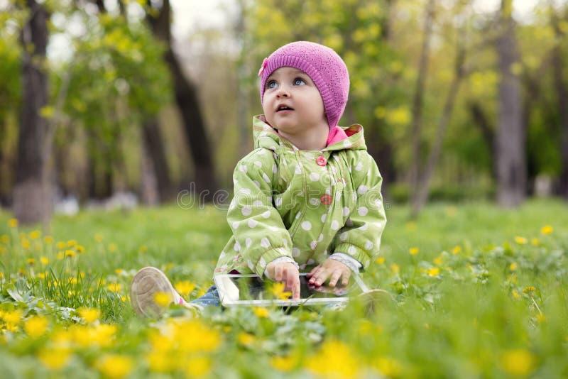 Barn som spelar med minnestavlan i parkera royaltyfria bilder