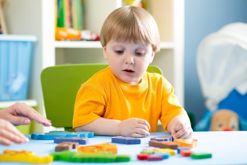 Barn som spelar med pusselleksaken inomhus arkivbilder