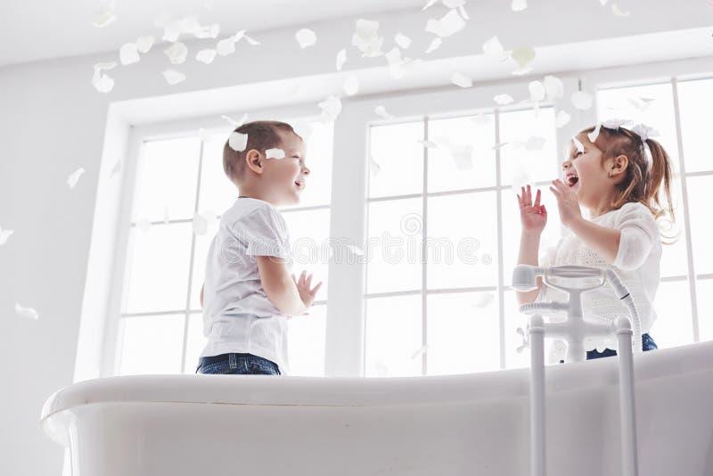 Barn som spelar med rosa kronblad i hem- badrum Liten flicka och fawing gyckel och glädje för pojke tillsammans Begreppet av fotografering för bildbyråer