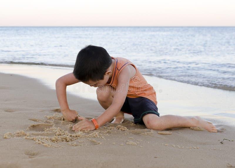 Barn som spelar med sand på stranden royaltyfria bilder