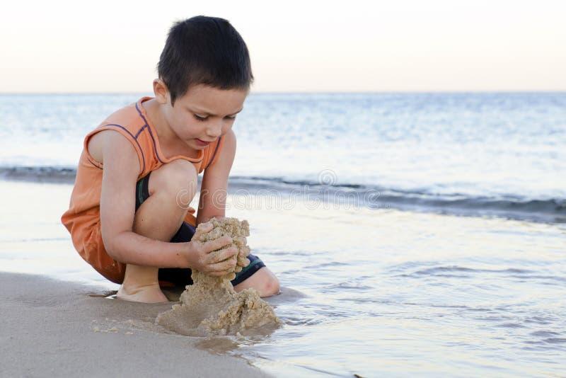 Barn som spelar med sand på stranden royaltyfri foto