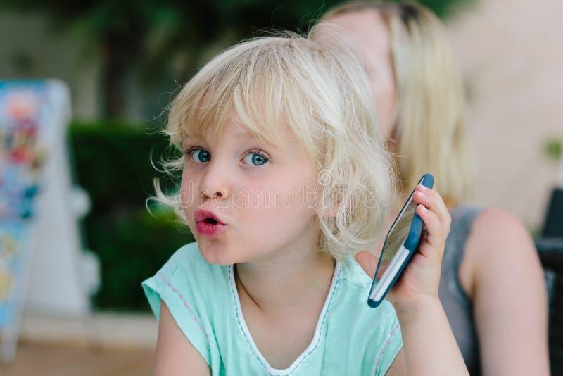 Barn som spelar med smartphonen royaltyfri fotografi