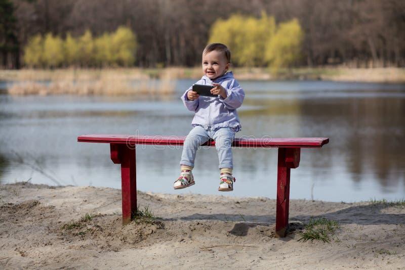 Barn som spelar med smartphonen i parkera royaltyfri bild