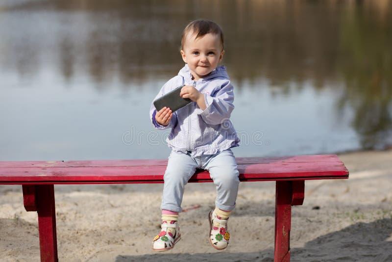 Barn som spelar med smartphonen i parkera royaltyfria foton