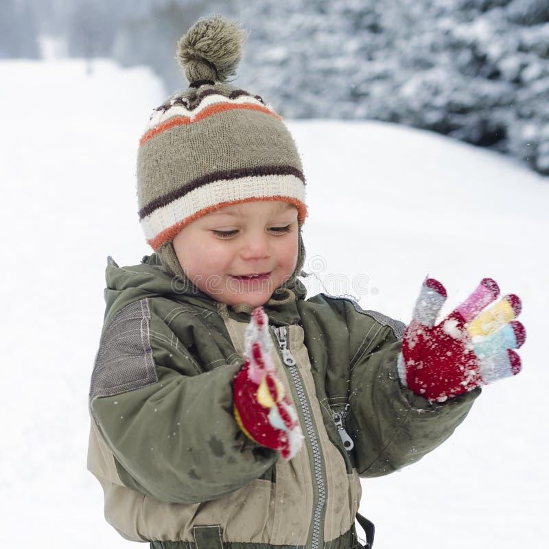 Barn som spelar med snö arkivfoton