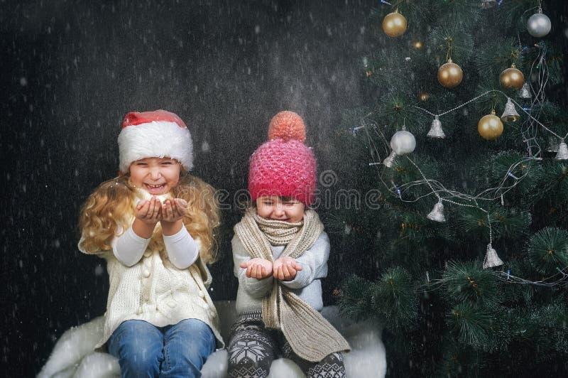 Barn som spelar med snöflingor på mörk bakgrund nära julgranen royaltyfri fotografi