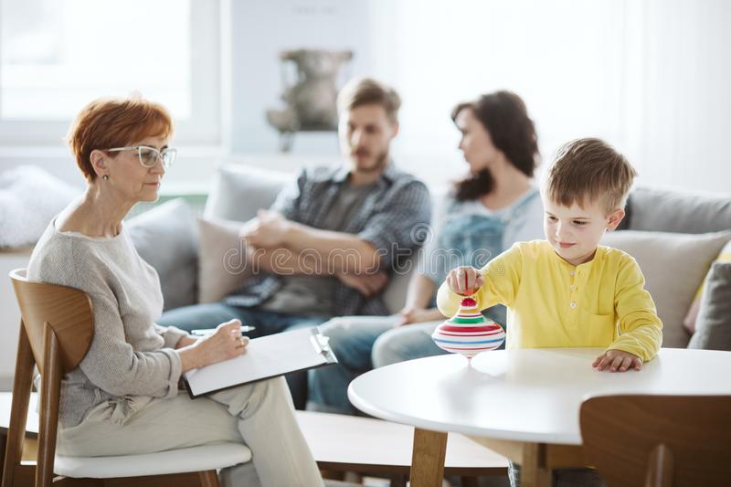 Barn som spelar med terapi f?r snurr?verkant ADHD med f?r?ldrar royaltyfria bilder