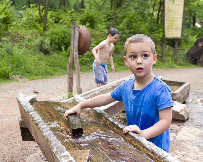 Barn som spelar med vatten parkerar in royaltyfria bilder