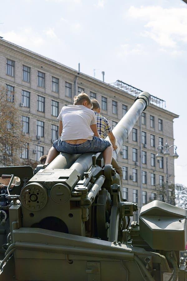 Barn som spelar militär utrustning under utställningen i Kiev September 23, 2017 royaltyfri foto