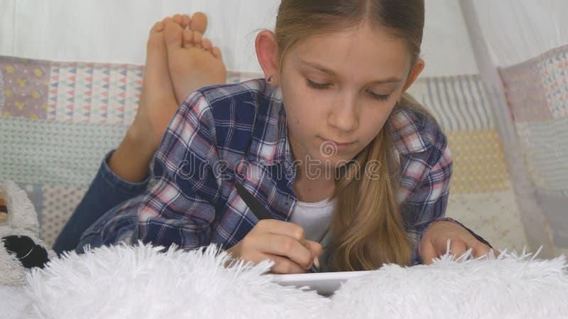 Barn som spelar minnestavlan i lekrumflickan som skriver läxa för skolaungelekplats arkivbilder