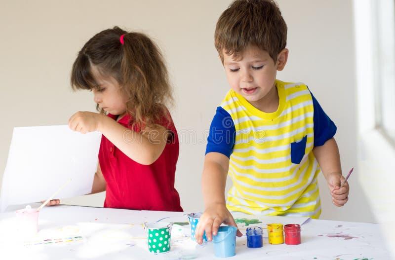 Barn som spelar och drar som är hemmastadd, eller dagis eller playschool arkivfoton