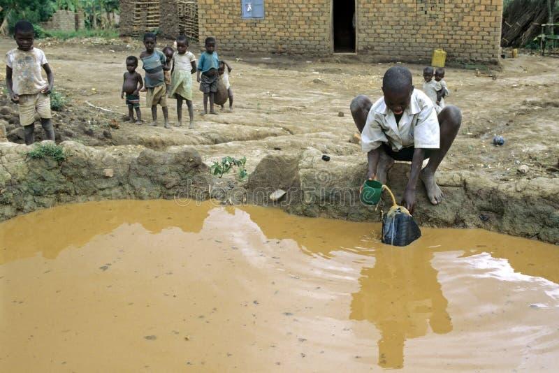 Barn som spelar, och smutsigt vatten för pojkefetch från brunnen arkivfoto