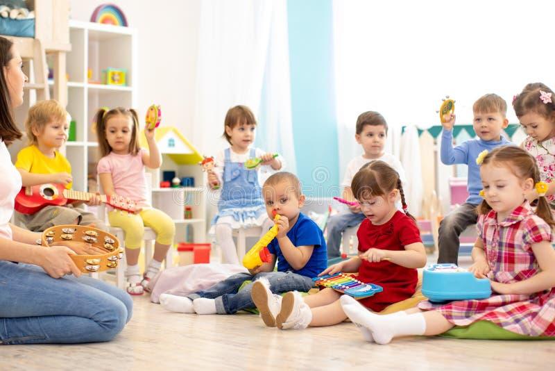 Barn som spelar olik musikalisk leksaker Tidig musikalisk utbildning i dagis fotografering för bildbyråer