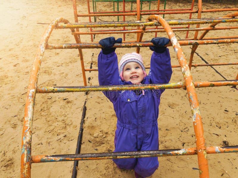 Barn som spelar på lekplatsen på kall vårdag arkivfoton