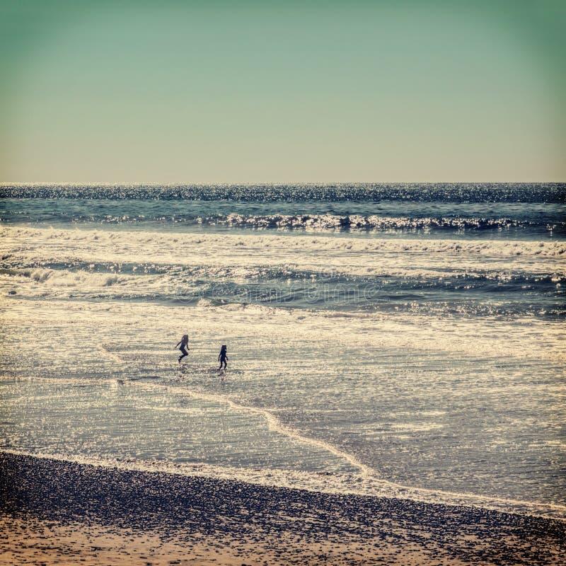 Barn som spelar på stranden arkivbilder
