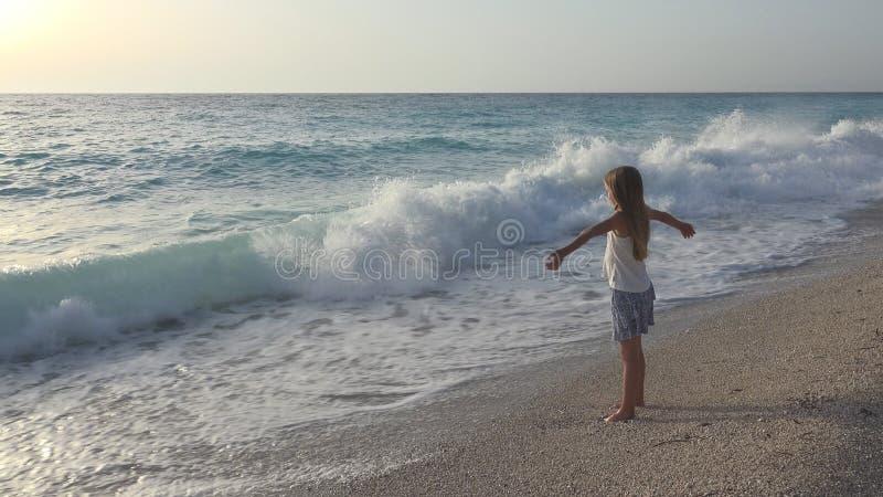 Barn som spelar på stranden, flicka som ser havsvågor, unge som håller ögonen på på kusten arkivbild