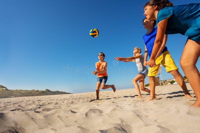 Barn som spelar strandvolleyboll under semester på havet royaltyfri fotografi
