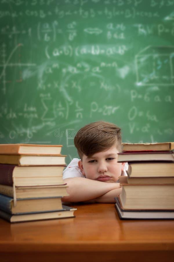 Barn som studerar på skrivbordet som ser borrat och under spänning med en tir arkivfoto