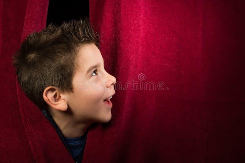 Barn som syns under gardinen arkivfoto
