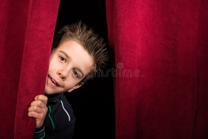 Barn som syns under gardinen royaltyfri foto