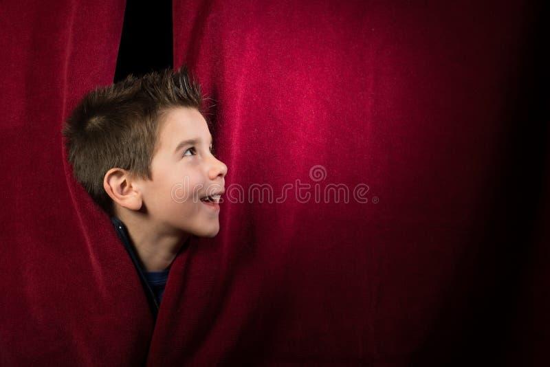 Barn som syns under gardinen royaltyfri fotografi