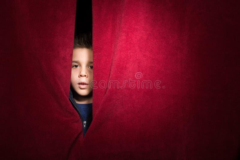 Barn som syns under gardinen arkivbild