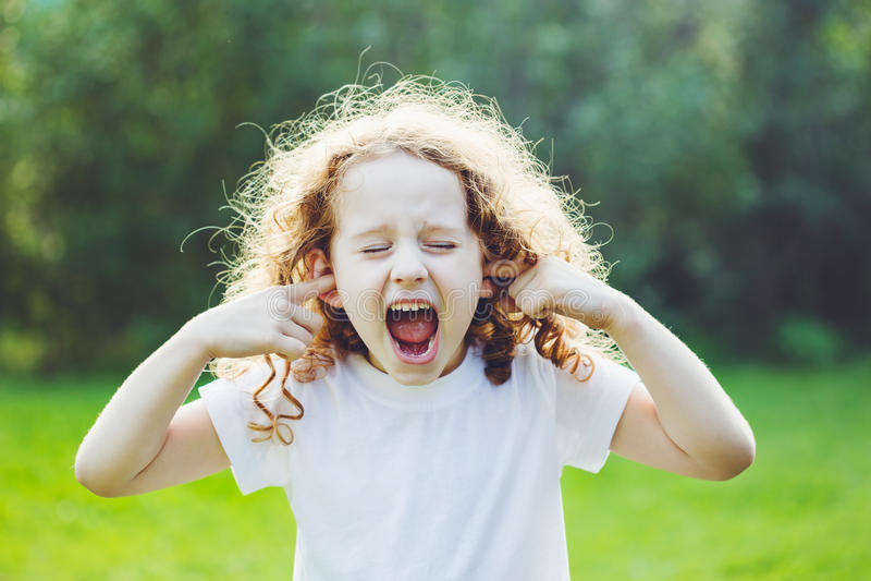 Barn som täcker henne öron och skrin fotografering för bildbyråer