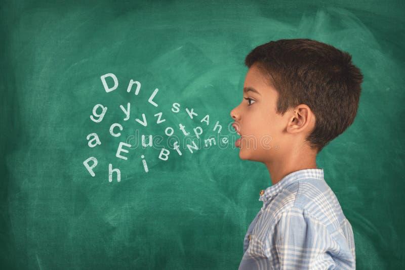 Barn som talar, och alfabetbokstäver som kommer ut ur hans mun royaltyfria bilder