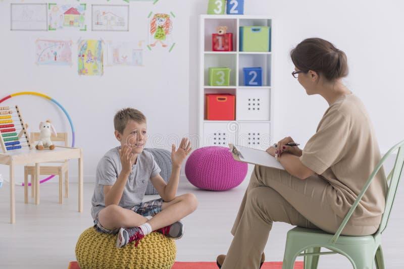Barn som talar till terapeuten royaltyfri bild