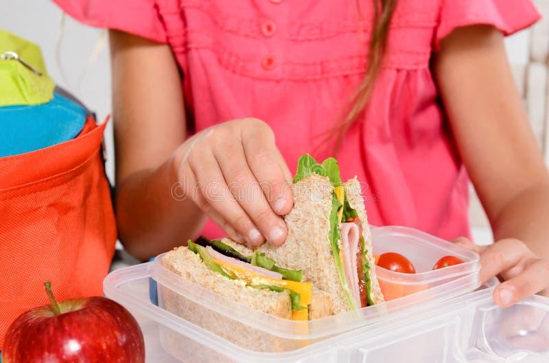 Barn som tar bort wholemealsmörgåsen ut ur lunchboxen arkivbild