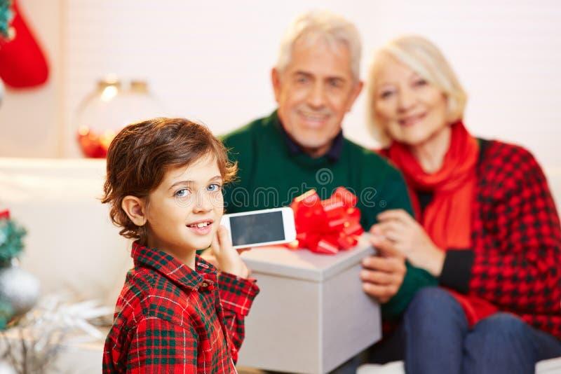 Barn som tar smartphonebilden av morföräldrar arkivfoto