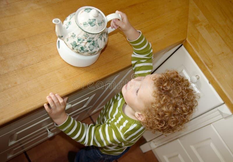 barn som tar teapoten royaltyfri foto