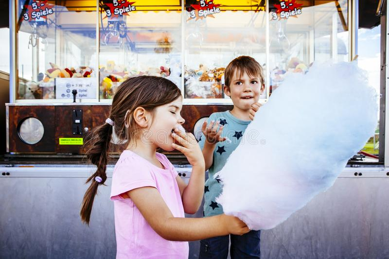 Barn som ?ter sockervadden p? karnevalet royaltyfri fotografi